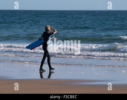 Middle aged woman heading for the sea with a bodyboard, Cornwall, UK - Stock Image