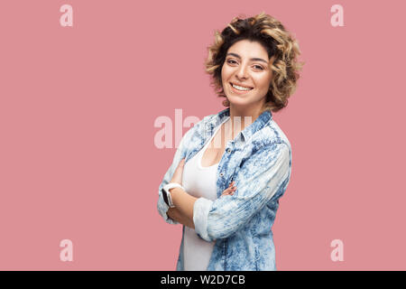 Portrait of beautiful successful happy young woman with curly hairstyle in casual blue shirt standing crossed arms and looking at camera, toothy smile - Stock Image