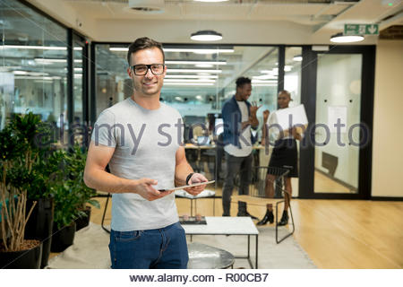 Smiling young businessman holding tablet in office - Stock Image