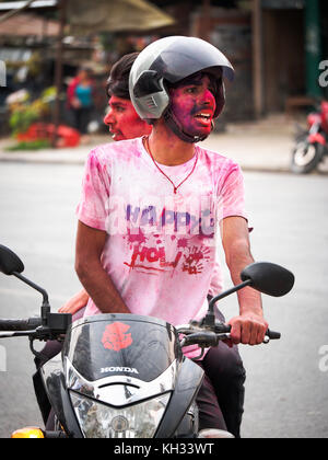 Young Nepali men covered with coloured powder return home on a scooter after celebrating the Hindu festival Holi - Stock Image