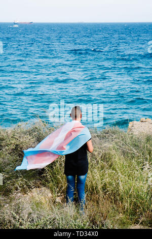 a young caucasian person, seen from behind, draping a transgender pride flag over his or her shoulders, facing the ocean - Stock Image