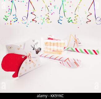 Christmas Decoration with cake slice gift boxes with cake piece and candy canes and confetti bursting for best background - Stock Image