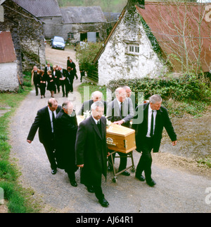 Pallbearers carry casket from traditional Welsh farmhouse at a farmers funeral Llanwrda Carmarthenshire Wales UK  KATHY DEWITT - Stock Image