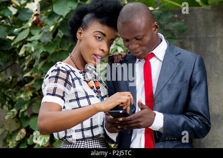 This young woman touches the screen of the mobile phone of his colleague. - Stock Image