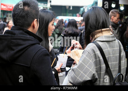 Young Chinese people tourists eating snack food, brownies at outdoor street food Borough Market in Southwark South London UK   KATHY DEWITT - Stock Image