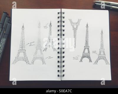 Hand-drawn Eiffel Tower sketches. Practicing freehand drawing of landmark on white notebook paper with pens and - Stock Image