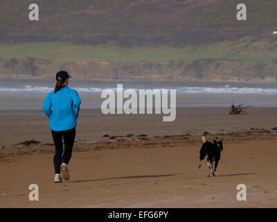 Jogger with her dog on an empty beach in winter, Saunton Sands, Devon, UK - Stock Image