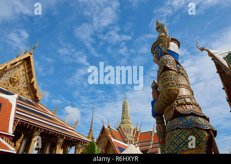 Yaksha statue in the Grand Palace facing a temple entrance in Bangkok, Thailand. The demon-gods statues are a common sight in Buddhist temples in Thai - Stock Image