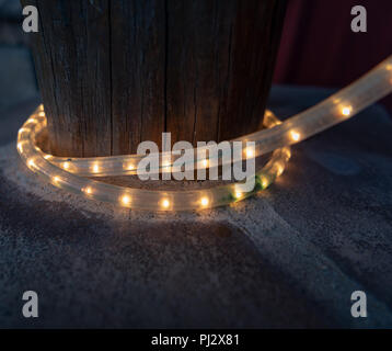 Tube of Lights Wrapped Around Wooden Post along sidewalk - Stock Image