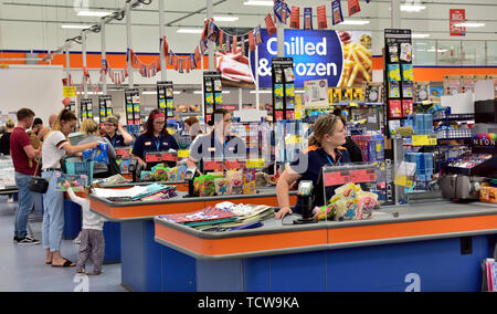 Staff at checkouts in B&M discount store ready to help customers - Stock Image