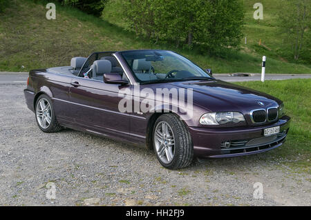 BMW 3 series convertible (model E46) with retracted roof in violet (eggplant) color. - Stock Image