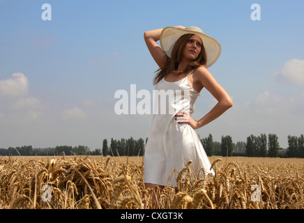A Young Woman Wearing a White Dress and Hat in a Corn Field. UK. - Stock Image
