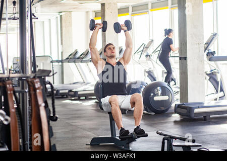 Portrait of young adult sport man training at gym alone. athlete working out in a gym, sitting and holding two dumbbell with raised arms, swinging sho - Stock Image