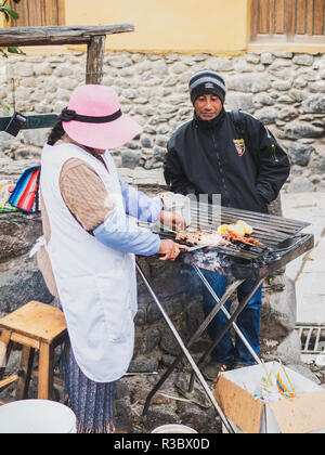 Ollantaytambo, Peru - January 5, 2017. A woman selling street food in the Ollantaytambo streets - Stock Image