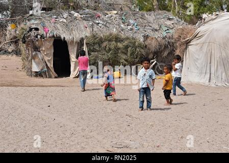Aden, Yemen. 16th Feb, 2019. Displaced children walk past their hut on the outskirts of Aden, Yemen, on Feb. 16, 2019. Hundreds of families were displaced from different war-torn Yemeni areas because of the ongoing fighting between the warring factions. Credit: Murad Abdo/Xinhua/Alamy Live News - Stock Image
