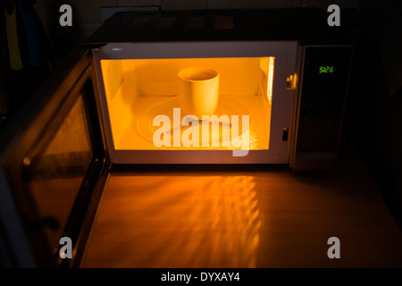 A reheated cup of coffee in a microwave. - Stock Image