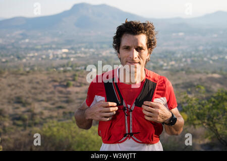 A fit, athletic middle aged man grabs his hydration vest while looking at the camera for a portrait as the fading sun side lights him in the mountains - Stock Image