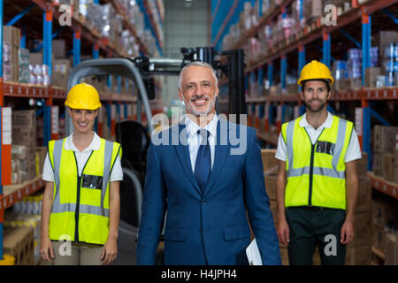 Portrait of warehouse manager and co-workers standing with clipboard - Stock Image