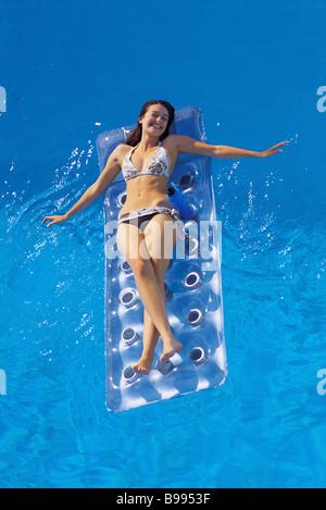 Girl lying on air mattress in pool - Stock Image