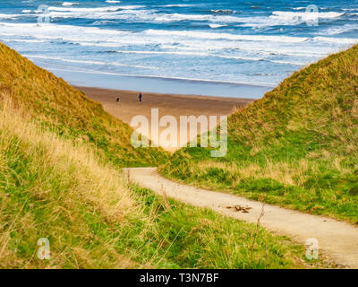 A steep bridle way for horse riders access down the cliff between Marske and Saltburn on the North Yorkshire Coast a man and his dog on the beach - Stock Image