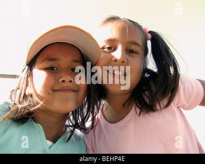 Girls sitting on baseball stands - Stock Image