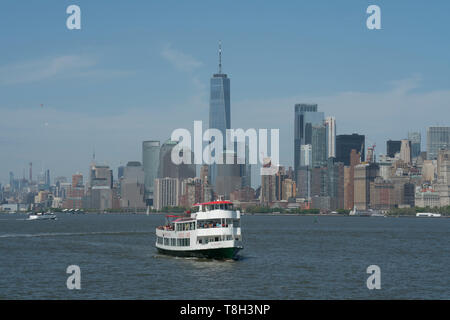 The skyline of Lower Manhattan with a Circle Line sightseeing boat taking tourists around New York Harbor. May 8, 2019 - Stock Image