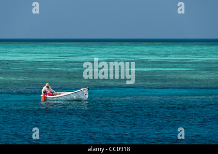 A man and his son explore the coral from a small dinghy on Swains Reef on the Great Barrier Reef. The small boy - Stock Image