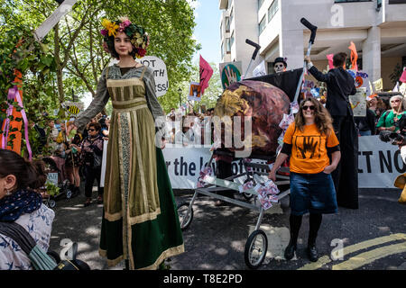 London, UK. 12th May 2019. A stilt walker and one of the giant pushchairs carrying a globe which followed behind 11-year-olds at the front of the Mothers Day March by thousands from Hyde Park Corner to a rally filling Parliament Square, backing Extinction Rebellion's call for the drastic and urgent action needed to avert the worst consequences of climate change, including possible human extinction. Our politicians have declared a climate emergency but now need to take real action rather than continuing business as usual which is destroying life on our planet. Peter Marshall/Alamy Live News - Stock Image