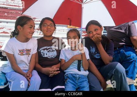 Girls watch horse races from under umbrella, during Yazzie Benefit Horse Race, at Jeddito, Navajo Indian Nation, - Stock Image
