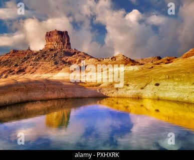 Hiker near reflection pool on banks of Lake Powell, Utah - Stock Image
