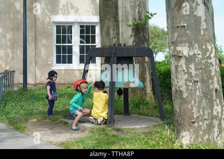 Two boys rang a large bell on Governors Island as a little girl watched them sadly, shut out from their fun. June 15, 2019 - Stock Image
