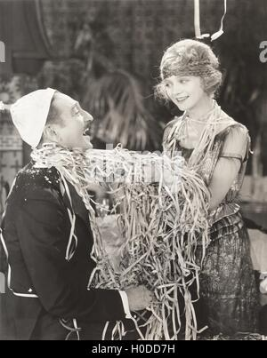 Man and woman covered in streamers - Stock Image
