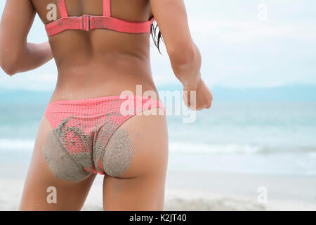 Sexy sandy butt of an attractive woman at a beach. Mid body section. - Stock Image