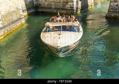 SIRMIONE, LAKE GARDA, ITALY - SEPTEMBER 2018: Visitors to Sirmione on Lake Garda taking a trip around the moat of Scaliger Castle in a motor launch, - Stock Image