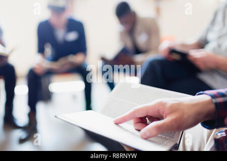 Close up man reading bible in prayer group - Stock Image