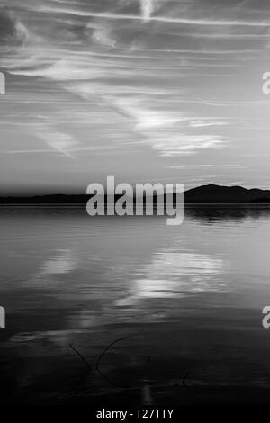 Beautiful view of Trasimeno lake (Umbria, Italy) at sunset, with cloud shapes on the sky. - Stock Image