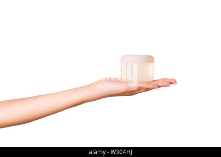 Female hand holding cream bottle of lotion isolated. Girl give cosmetic products on white background. - Stock Image