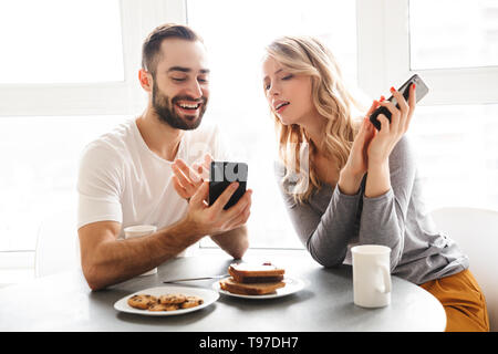 Image of amazing young loving couple sitting at the kitchen have a breakfast using mobile phones. - Stock Image