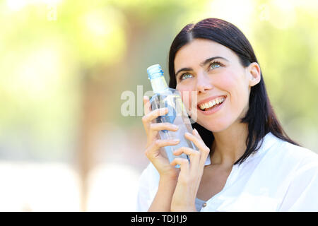Happy woman holding a bottle of water looking above standing in a park with a green background - Stock Image