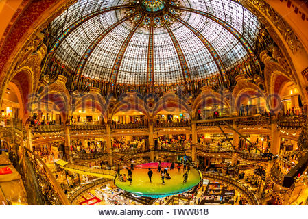 A trampoline suspended below the stained glass dome (and above, to the right, the Glass Walk) of Galeries Lafayette Paris Haussmann department store, - Stock Image