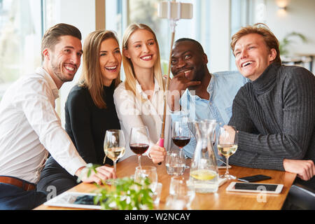 Young people take a selfie photo with the selfie stick in the restaurant or pub - Stock Image