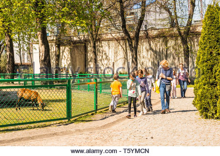 Poznan, Poland - April 18, 2019: Older women with small group of kids walking on a pathway next to a fence with goat in the old zoo on a sunny spring  - Stock Image