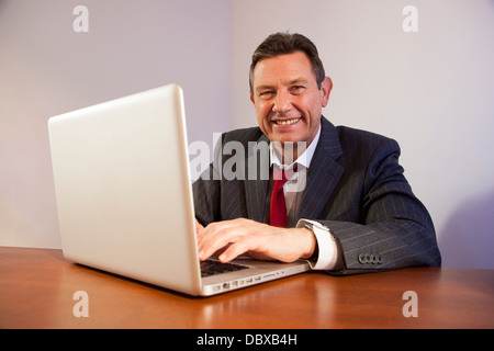 Business man at a desk using a laptop computer, looking at camera smiling. - Stock Image