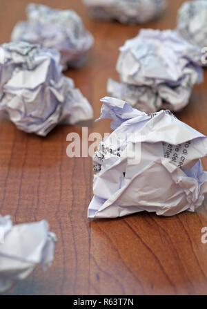 crumpled paper balls on desk - Stock Image