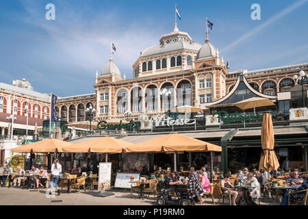 People sitting at busy cafe tables outside the Holland Casino building, Scheveningen, Den Haag (The Hague), Netherlands. - Stock Image