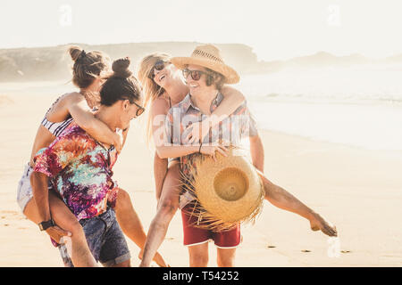 Cheerful friends couple of people girls and boys have fun together at the berach in summer holiday vacation together - men carrying the women and ever - Stock Image