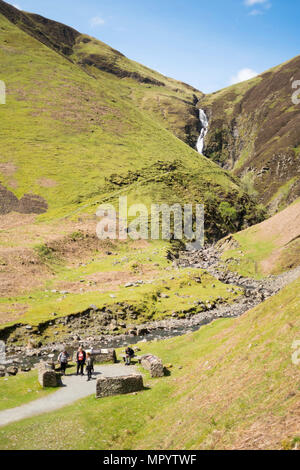 A group of visitors at the viewpoint beneath The Grey Mare's Tail or Roaring Linn waterfall, near Moffat, Dumfries & Galloway, Scotland, UK - Stock Image
