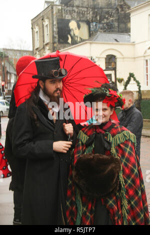 Rochester, Kent, UK. 1st December 2018: A couple in Period Victorian costume ahead of the main parade on Rochester High Street. Hundreds of people attended the Dickensian Festival in Rochester on 1 December 2018. The festival's main parade has participants in Victorian period costume from the Dickensian age. The town and area was the setting of many of Charles Dickens novels and is the setting to two annual festivals in his honor. Photos: David Mbiyu/ Alamy Live News - Stock Image
