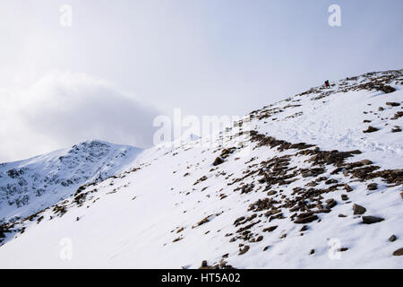 View to Y Garn summit peak from ridge with hiker hiking in winter snow in Snowdonia National Park mountains. Ogwen, - Stock Image