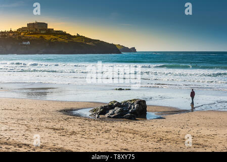 A man walking alone in the evening light on Great Western Beach in Newquay in Cornwall. - Stock Image